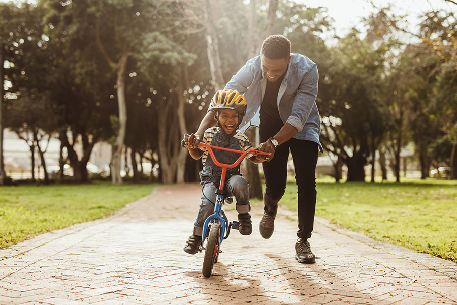 Contact - Father Teaching Excited Son How To Ride A Bike In The Park