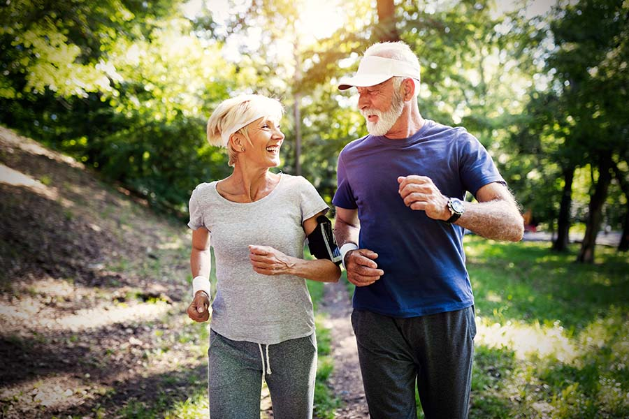 Employee Benefits - Older Couple Smiling While Jogging Through Trail In Forest