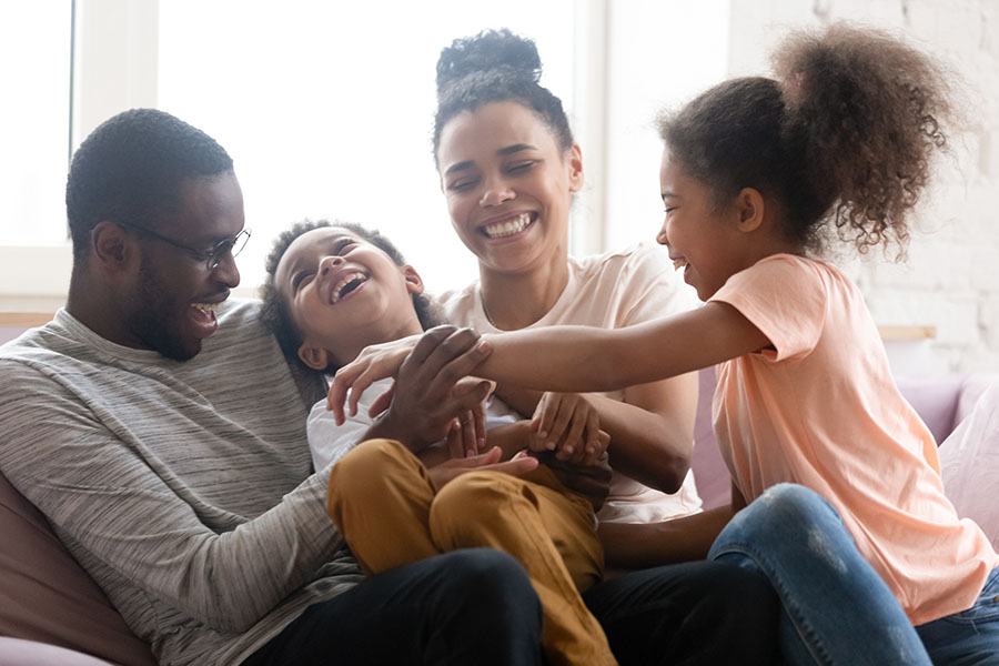 Personal Insurance - Happy Family Of Four Sitting On Couch At Home Playing
